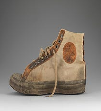 """Converse All Star/Non Skid, 1917In 1917, the company then known as Converse Rubber Shoe Co. introduced a brown canvas high-top called the """"All Star,"""" while the white canvas model shown here was sold as the """"Non Skid."""" The two styles shared the rubber toe cap, license plate at the heel, and circular ankle patch. When basketball coach Chuck Taylor started endorsing the sneakers in 1921, the ankle patch took on his name, and the iconic sneaks we call """"Chucks"""" were born."""