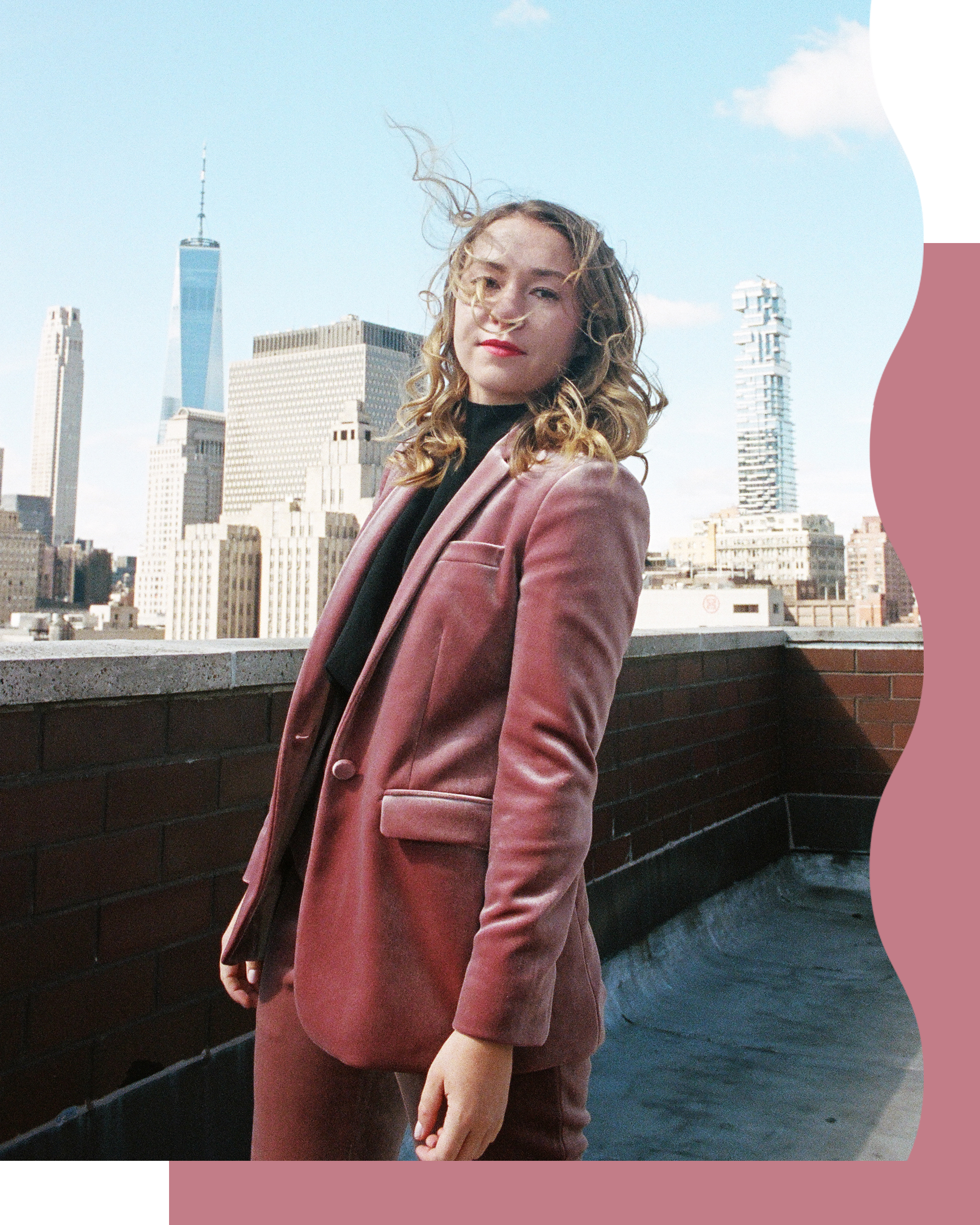 Polly Rodriguez in a pink velvet suit on a nyc roof top.