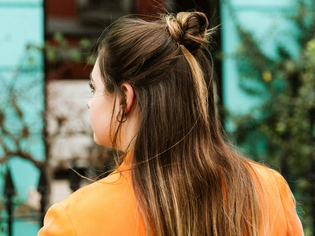 Woman wearing an orange blazer shot from behind showing her long brown hair with highlights